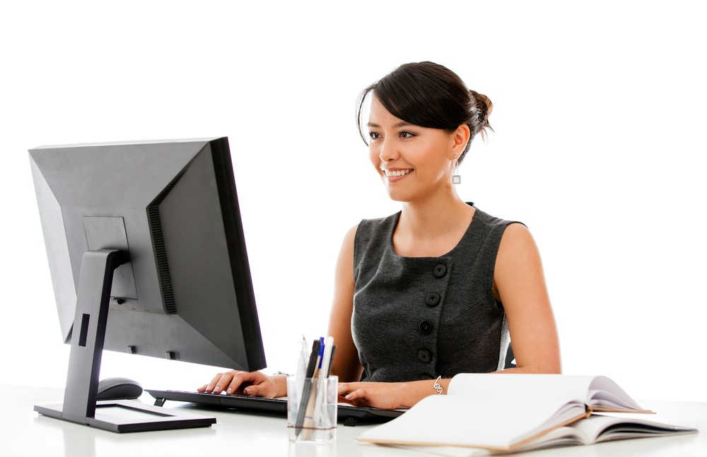 Businesswoman at the office working on a computer - isolated.jpeg
