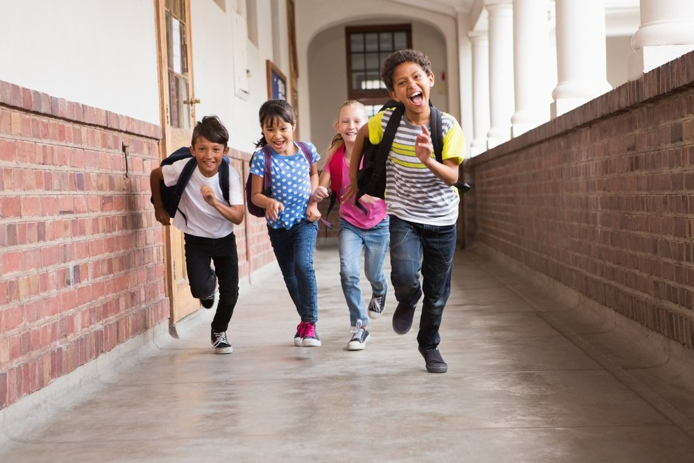 Cute pupils running down the hall at the elementary school