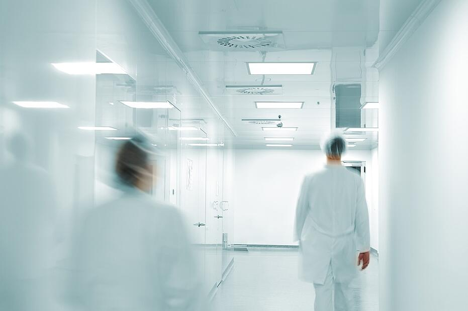 Working people with white uniforms walking in modern  factory environment