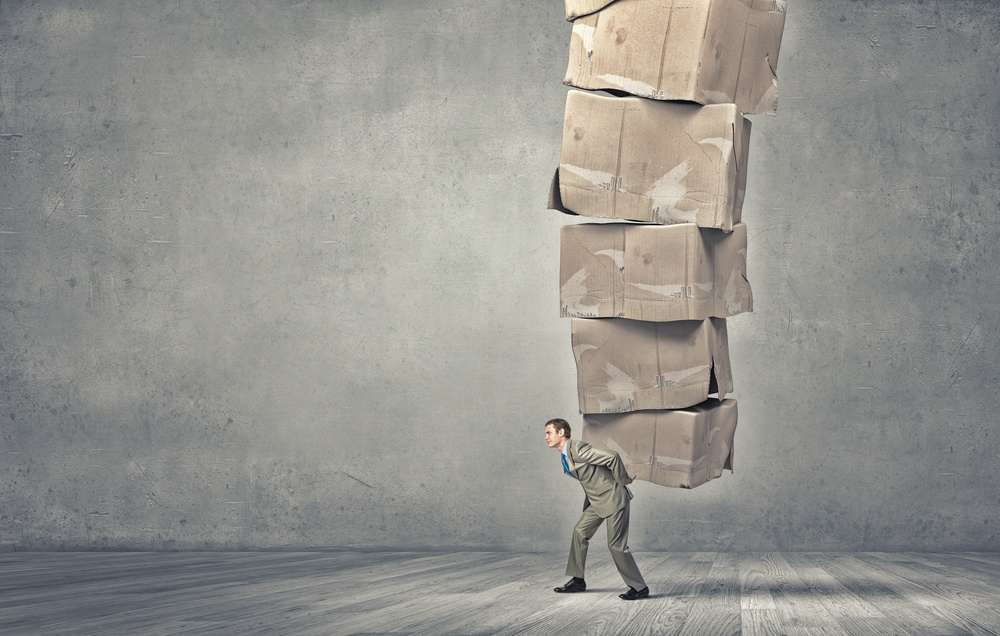 Young businessman in suit carrying big stack of carton boxes.jpeg