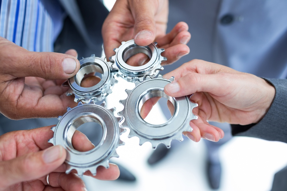 Business colleagues holding cog in the office