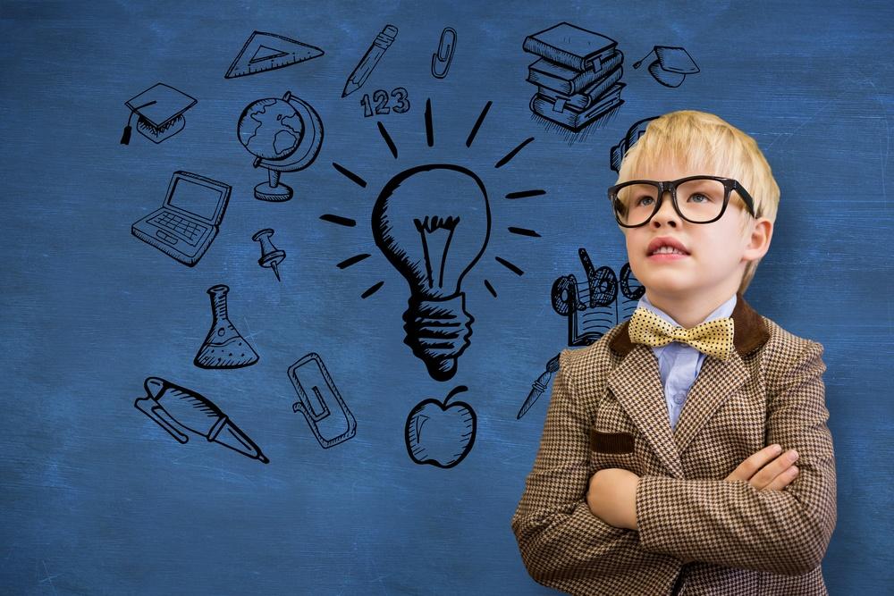 Cute pupil dressed up as teacher against blue chalkboard.jpeg