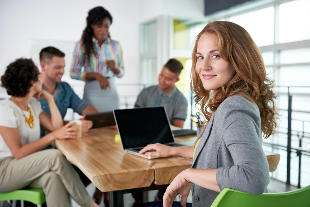 Image of a succesful casual business woman using laptop during meeting